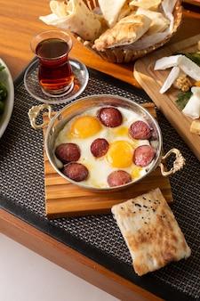 Eine wurst von oben mit eiern zusammen mit tee- und brotlaib auf dem tisch des restaurants