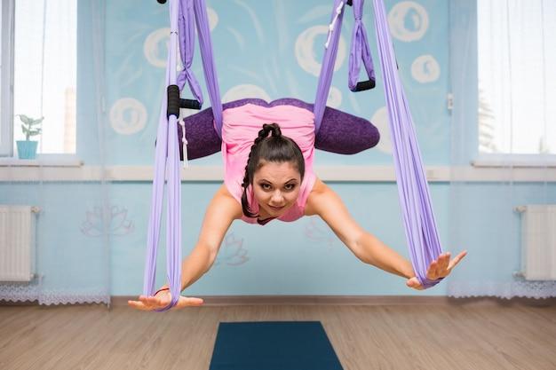 Eine yoga-frau in sportkleidung führt asanas in einer hängematte im studio durch