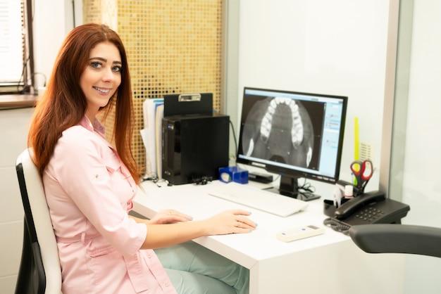 Eine zahnärztin sitzt an einem tisch, auf einem computer ein ct des kiefers. der arzt ist in berufskleidung gekleidet.