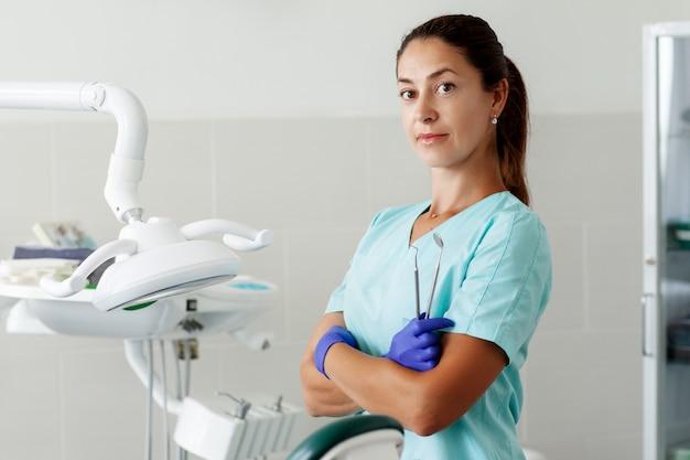 Eine zahnärztin sitzt auf einem stuhl und lächelt, während sie werkzeuge in ihren händen hält.