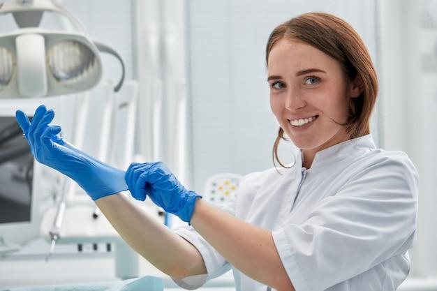 Eine zahnärztin zieht in einer zahnarztpraxis handschuhe an. glückliches patienten- und zahnarztkonzept.