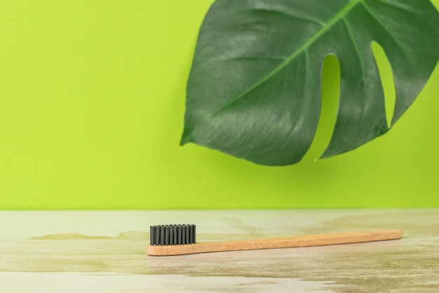 Eine zahnbürste mit schwarzen borsten und einem holzgriff auf dem hintergrund eines großen grünen blattes.