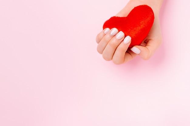 Eine zarte weibliche hand hält ein weiches rotes herz auf einem rosa hintergrund mit leerer werbefläche.