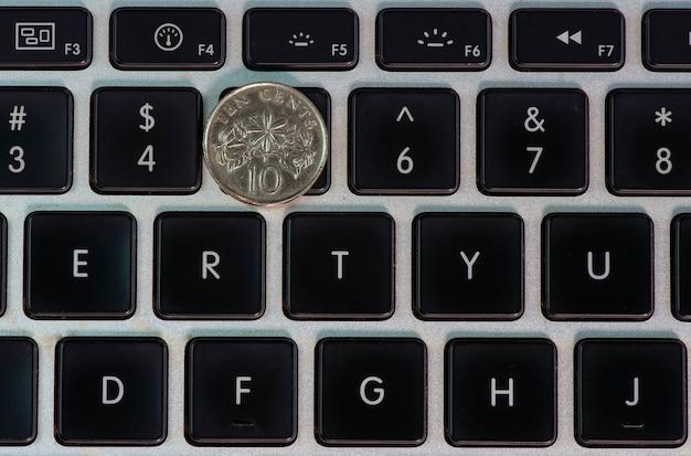 Eine zehn-cent-singapur-münze auf der computertastatur
