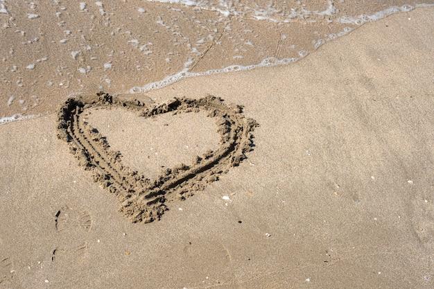 Eine zeichnung eines herzens auf einem gelben sand an einem schönen seestückhintergrund. horizontale zusammensetzung.