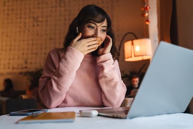 Eine ziemlich schockierte positive frau drinnen im café mit kopfhörern mit laptop-computer.