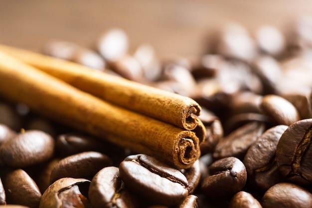 Eine zimtstange liegt auf der nahaufnahme der gerösteten kaffeebohnen