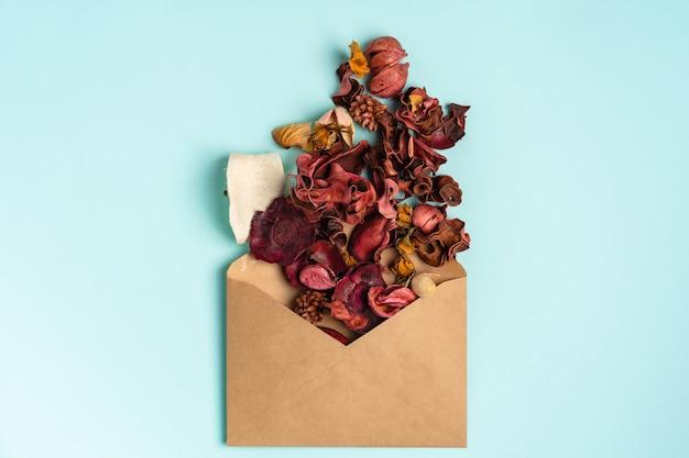 Eine zusammensetzung von getrockneten blütenblättern und blättern auf einem blauen hintergrund, ein romantisches konzept