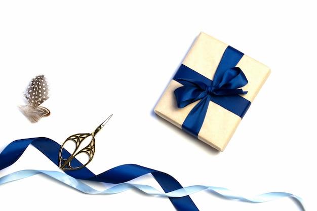 Eine zusammensetzung von verpackten geschenken, kraftpapier und blauem band lokalisiert auf einem weißen hintergrund. der blick von oben. zum modell einladung.
