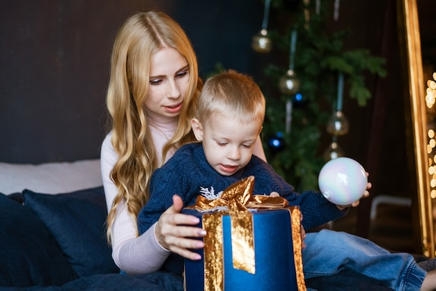 Eine zweiköpfige familie, mutter und sohn, die ein geschenk in der nähe des weihnachtsbaums auspacken, das konzept einer feiertagskr...