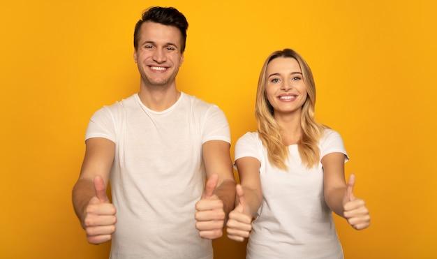 Eine zweiköpfige familie posiert auf gelbem hintergrund, trägt freizeitkleidung und drückt mit ihren posen und gesten glück und sieg aus.