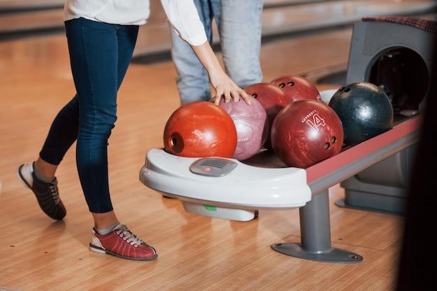 Einen ball nehmen. kurzansicht der leute im bowlingclub, die bereit sind, spaß zu haben