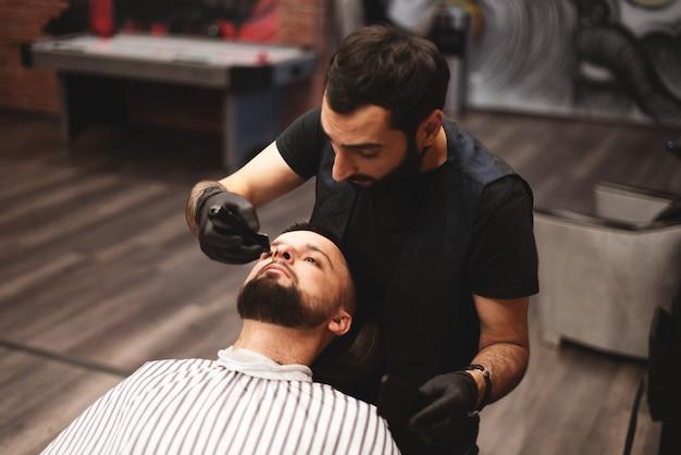 Einen bart im friseursalon mit einem gefährlichen rasiermesser rasieren. friseur bartpflege. trocknen, schneiden, bart schneiden.