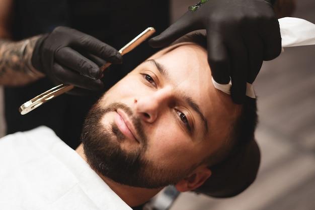 Einen bart in einem friseursalon mit einem gefährlichen rasiermesser rasieren. friseur bartpflege. trocknen, bart schneiden.