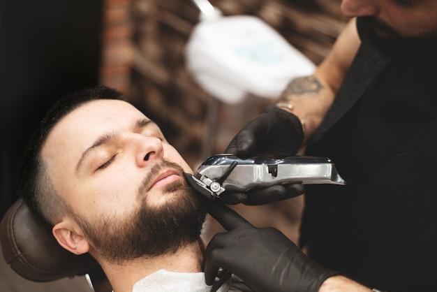 Einen bart in einem friseursalon mit einem gefährlichen rasiermesser rasieren. friseur bartpflege. trocknen, schneiden, bart schneiden. tiefenschärfe.