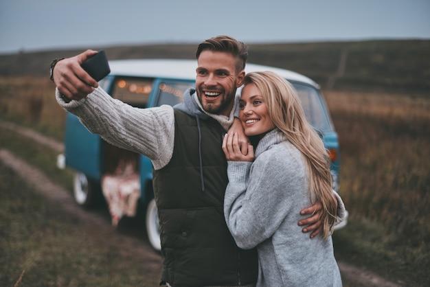 Einen glücklichen moment festhalten. schönes junges paar, das selfie nimmt und lächelt, während sie ihre straßenreise genießen