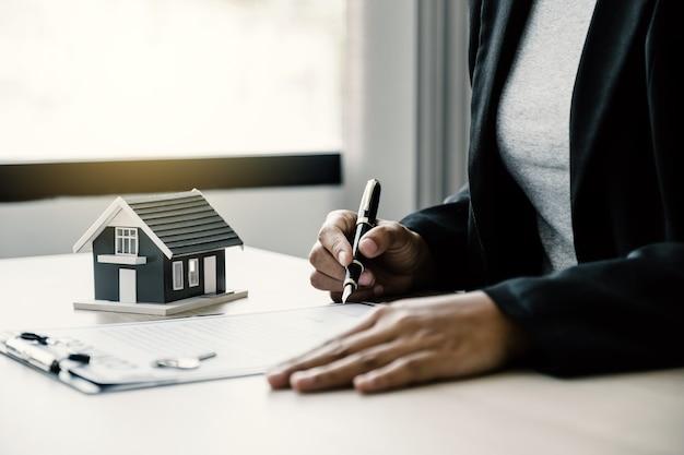 Einen immobilienmakler mit hausmodell übergeben und der käuferin die geschäftsvertragsversicherung erklären