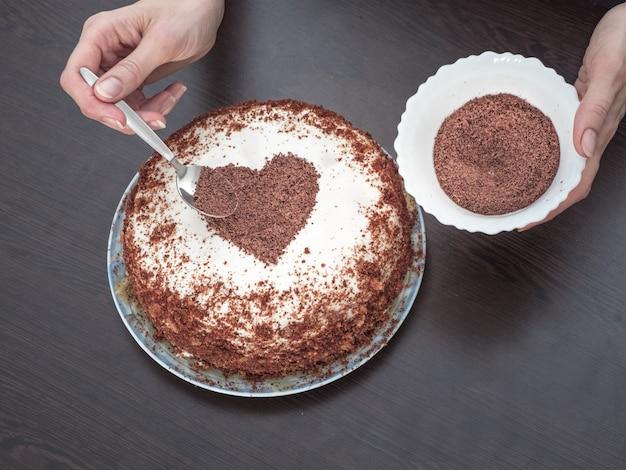 Einen kuchen zum valentinstag dekorieren. handgemachte torte mit frischkäse-zuckerguss und einem schokoladenherz. süßigkeiten zum valentinstag