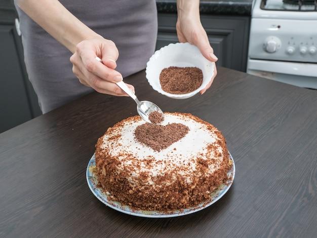 Einen kuchen zum valentinstag dekorieren. handgemachte torte mit frischkäse-zuckerguss und einem schokoladenherz.