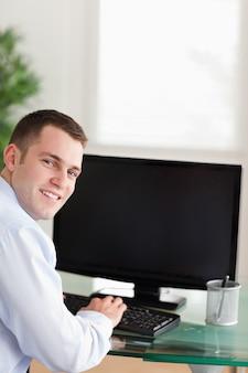 Einen lächelnden geschäftsmann schüchtern, der an seinem computer arbeitet