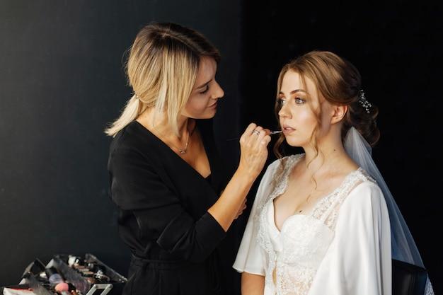 Einen lippenstift auftragen. hochzeits make-up. maskenbildner malt lippenstiftmädchen. make-up-künstler in bearbeitung in. schöne frau gesicht. mit abendlichem make-up. hand des make-up-meisters.