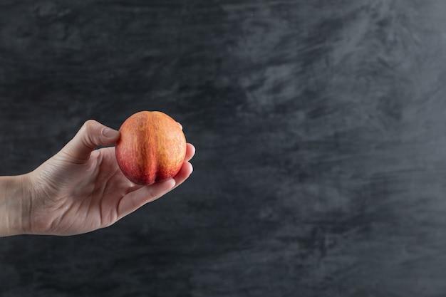 Einen roten pfirsich halten und auf schwarz tippen