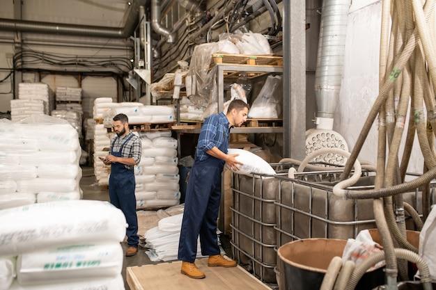 Einer der jungen arbeiter einer großen modernen fabrik streut polymerkörner vor dem arbeitsprozess in einen riesigen behälter