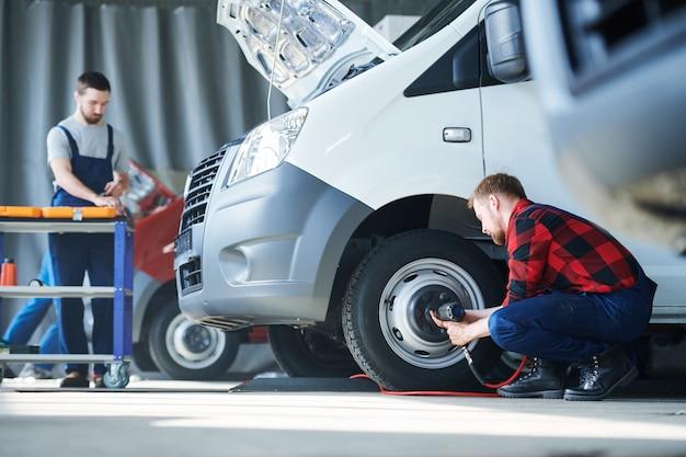 Einer der jungen autowerkstätten repariert raddetails, während sein kollege sich über den werkzeugkasten beugt