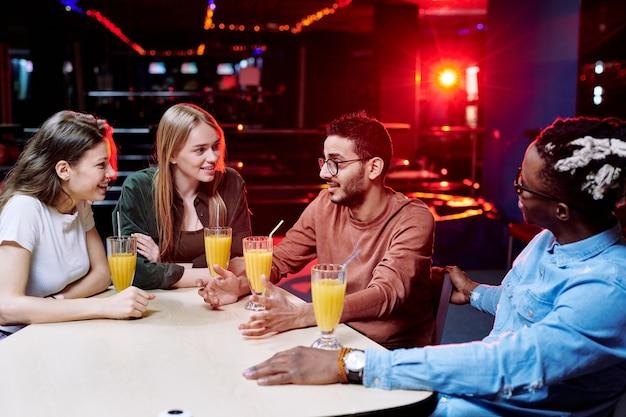 Einer der jungen, liebevollen interkulturellen freunde erklärt etwas, während andere ihn am tisch im café des freizeitzentrums ansehen