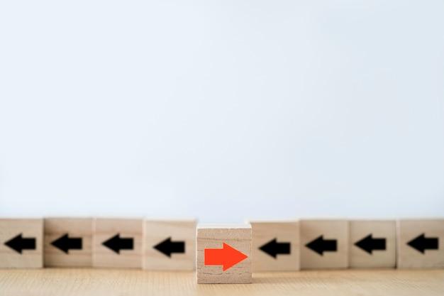 Einer der roten pfeile bewegt sich in die entgegengesetzte richtung, der andere der schwarze pfeil, der auf holzblockwürfeln geschnitzt ist