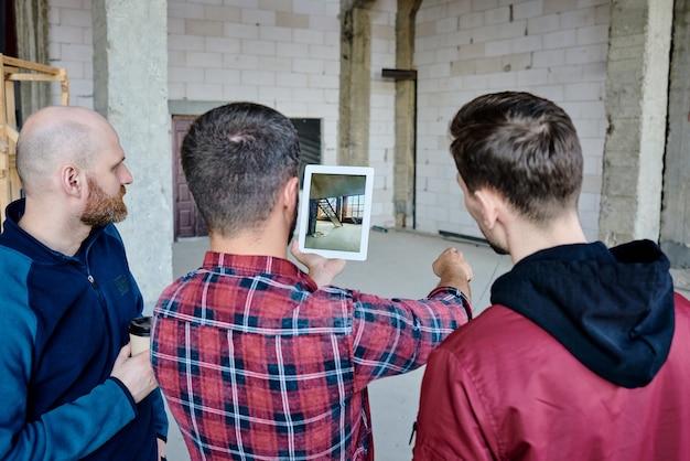 Einer der zeitgenössischen bauherren mit tablett zeigt seinen kollegen, wo sie beim start-up-meeting eine neue treppe bauen sollen