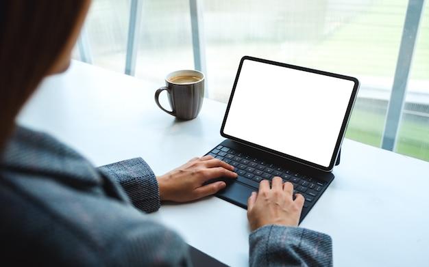 Einer frau, die auf tablet-tastatur mit leerem weißen desktop-bildschirm als computer-pc, kaffeetasse auf dem tisch verwendet und tippt