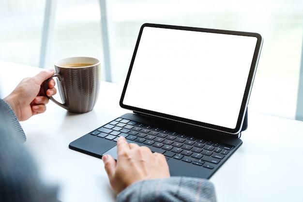 Einer frau, die ein tablet-touchpad mit einem leeren weißen desktop-bildschirm als computer-pc beim kaffeetrinken verwendet und berührt