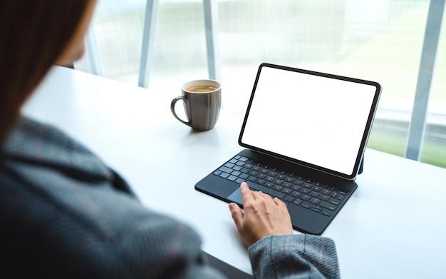 Einer frau, die ein tablet-touchpad mit einem leeren weißen desktop-bildschirm als computer-pc und eine kaffeetasse auf dem tisch verwendet und berührt