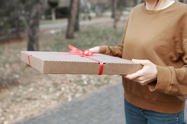 Einer frau ein geschenk geben. das konzept eines urlaubs, eine überraschung