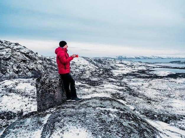 Einer oben. eine tasse heißen tee in der hand eines mannes auf einem polarhügel
