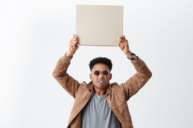 Einer von zehn. eww. porträt eines jungen attraktiven dunkelhäutigen mannes mit afro-frisur in freizeitkleidung und sonnenbrille, die leeren karton über kopf mit angewidertem ausdruck hält.