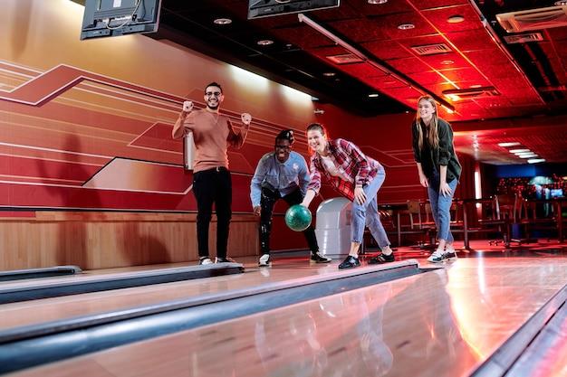 Eines der glücklichen mädchen wird bowlingkugel auf gasse werfen, während ihre freunde, die in der nähe stehen, freude während des spiels ausdrücken