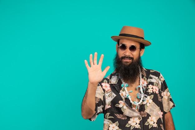 Eines glücklichen mannes mit einem langen bart, der einen hut trägt und ein gestreiftes hemd trägt, das eine geste auf einem blau zeigt.