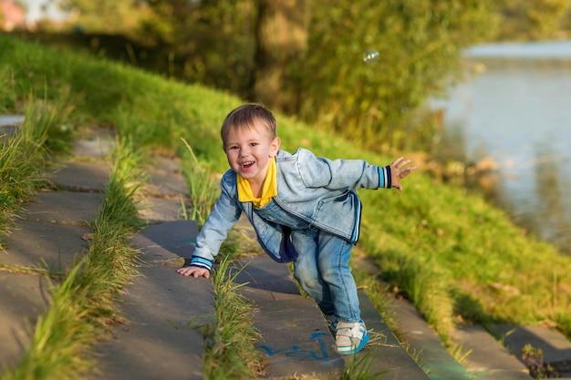 Eines sommerabends geht ein kleiner junge im öffentlichen park die treppe hinunter.