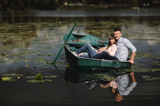 Einfach entspannen. schöne junge paare, die romantisches datum beim rudern eines bootes genießen. liebevolle paare, die auf einem see beim reiten eines grünen bootes stillstehen. romantik.
