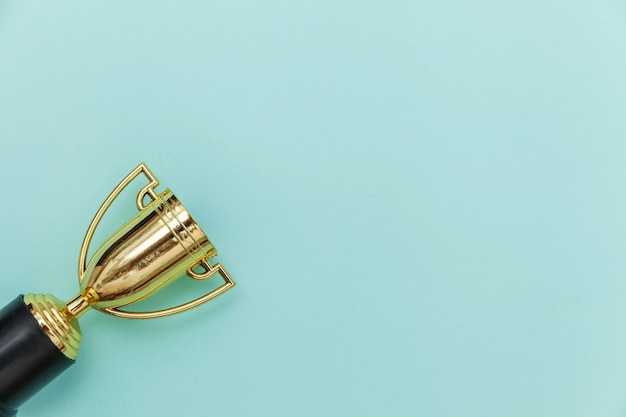 Einfach flach legen design gewinner oder champion gold trophäen tasse isoliert auf blau pastell bunten hintergrund