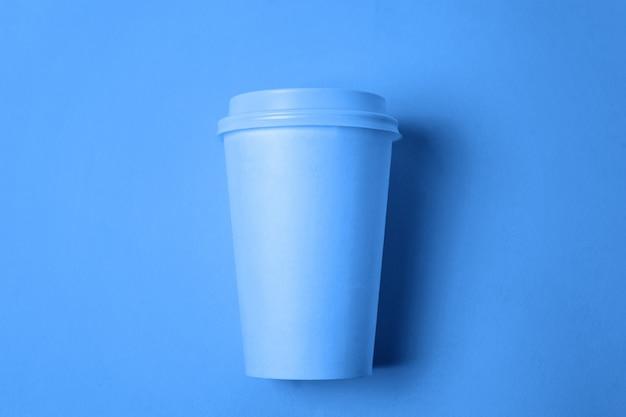 Einfach flach legen sie designpapierkaffeetasse, die in der modischen farbe des klassischen blauen hintergrundes 2020 gefärbt wird. helles makro unter verwendung der farbe. draufsicht copyspace