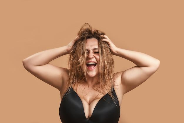 Einfach glücklich. positive pralle frau in schwarzer unterwäsche, die ihr haar berührt und lacht, während sie im studio gegen eine braune wand steht