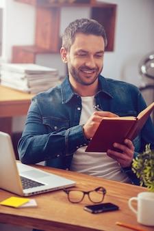 Einfach inspiriert. hübscher junger mann, der sein notizbuch betrachtet und lächelt, während er an seinem arbeitsplatz im büro sitzt