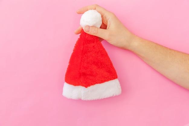 Einfach minimale frauenhand des designs weibliche, die weihnachtsverzierung sankt-hut lokalisiert auf buntem modischem pastellhintergrund hält