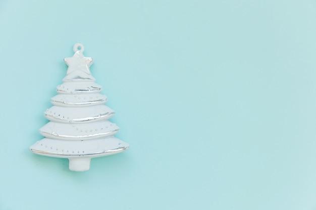 Einfach minimale zusammensetzung winterobjekt ornament tannenbaum isoliert auf blauem hintergrund