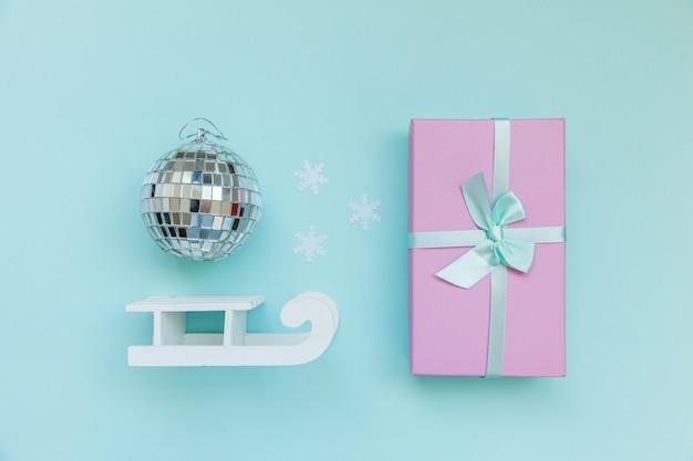 Einfach minimale zusammensetzung winterobjekte ornament ball schlitten geschenkbox isoliert auf blauem hintergrund