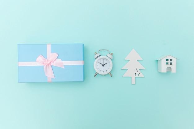 Einfach minimale zusammensetzung winterobjekte ornament tannenbaum ball geschenkbox isoliert blauen hintergrund