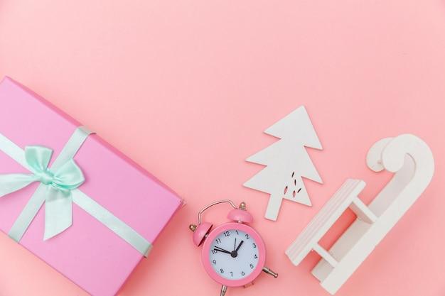 Einfach minimaler zusammensetzungswinter wendet verzierungsschlitten-tannenbaumball-geschenkbox lokalisierten rosa pastellhintergrund ein